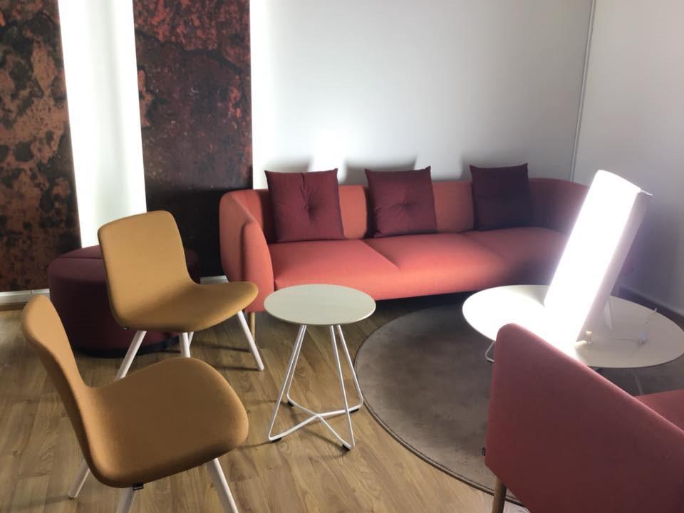 Huome, jossa sohva ja tuoleja puoliympyrässä kirkasvalon edessä.